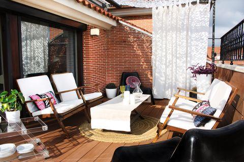 terraza con butacas de madera y alfombra de fibras