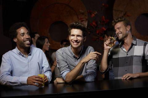 Cheerful friends enjoying drinks in nightclub