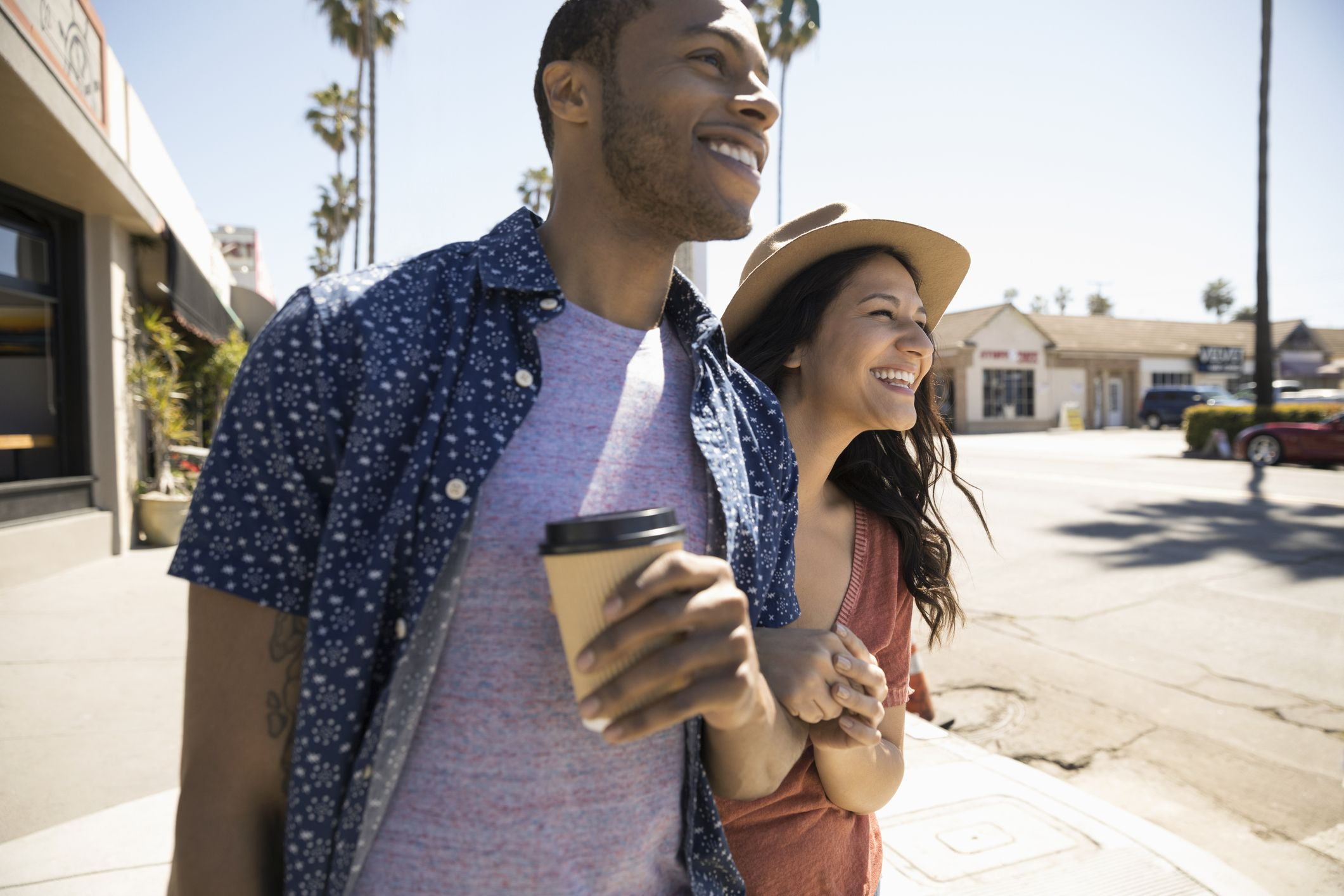 Smiling couple drinking coffee and walking on sunny sidewalk
