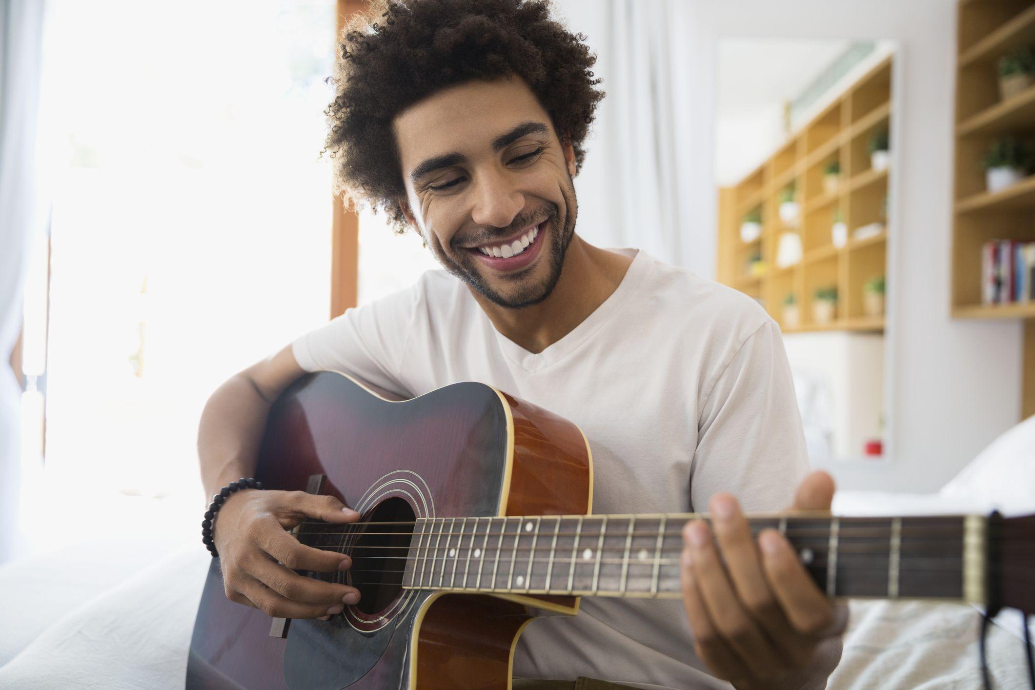 Smiling man playing guitar in bedroom
