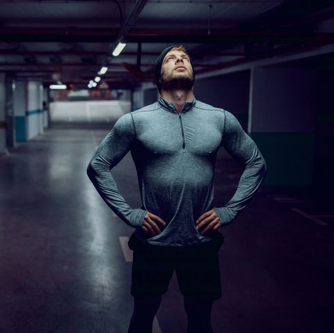 Attractive fit caucasian sportsman in active wear standing in garage with hands on hips and resting.