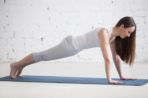 Attractive fit young woman doing plank pose in white