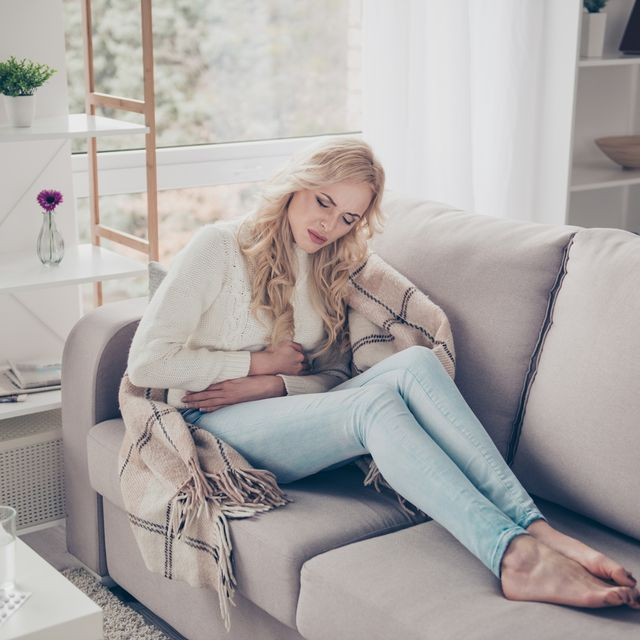 attractive slim stylish gloomy wavy haired lady housewife in sweater sitting on divan bare foot writhing in pain early term pregnancy digestion problem trouble disease in light white interior room