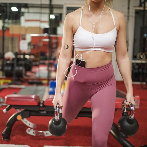 Attractive Woman doing kettlebell exercise at gym