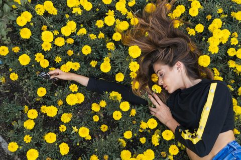 attractive young woman lying in flower meadow