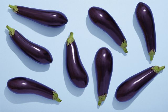 aubergines on blue background, eggplant flat lay