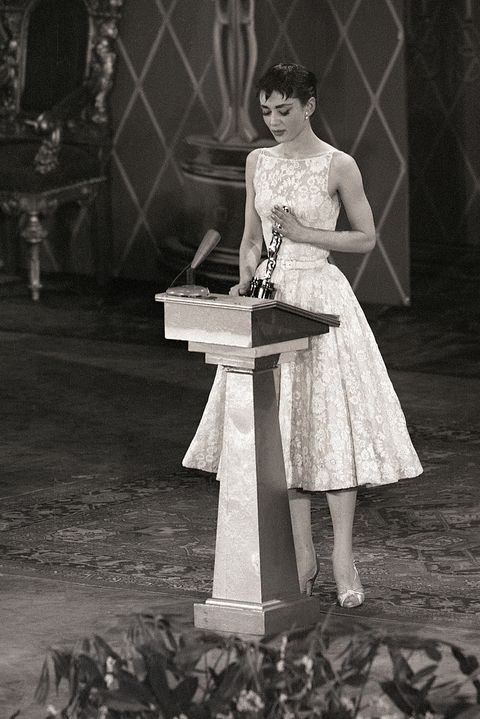 """original caption 3251954 new york  audrey hepburn smiles sweetly as she receives hollywood's highest accolade  an oscar for the best performance by an actress  from jean hersholt at the center theater tonight the 22 year old stage and screen star won her award for her only american film, """"roman holiday"""""""