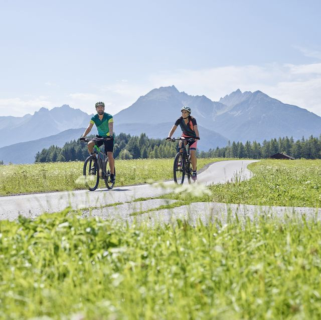Austria, Tyrol, Mieming, couple riding bike in alpine scenery