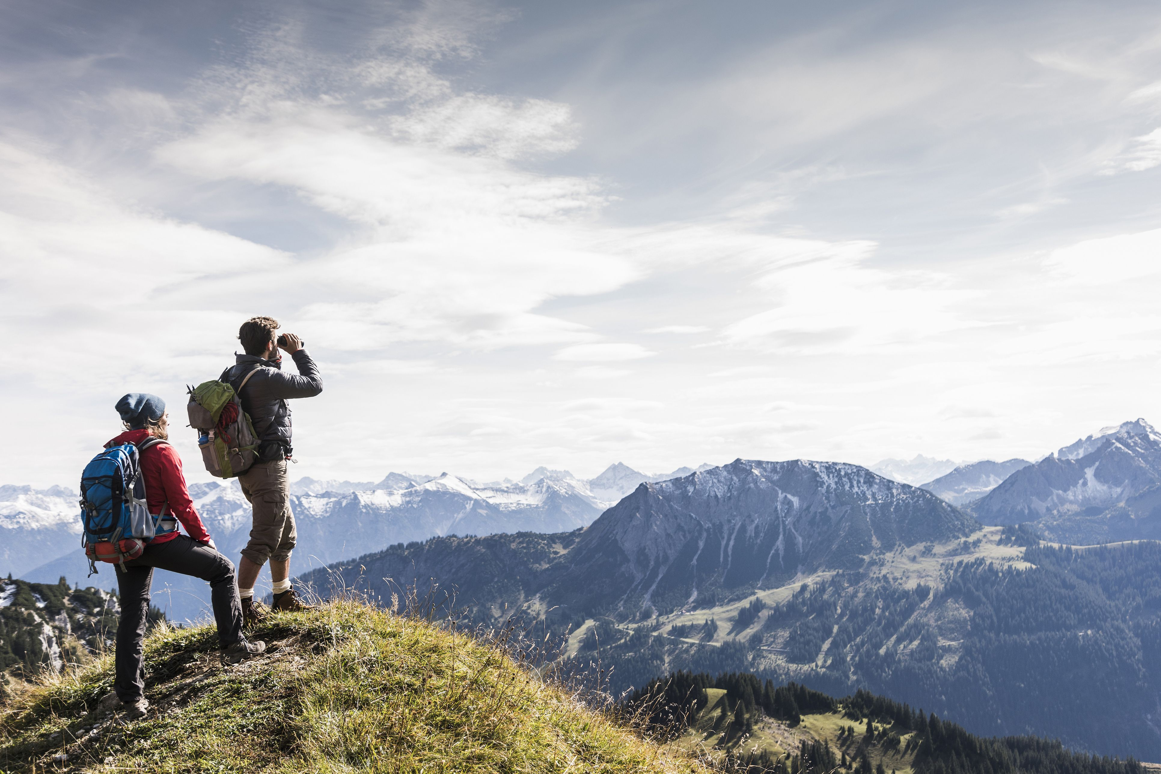 Austria, Tyrol, young couple standing in mountainscape looking at view
