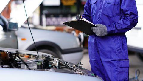 automotive mechanic doing vehicle maintenance checklist
