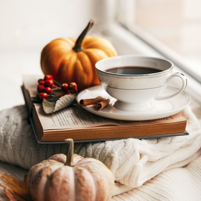 autumn morning coffee cup of coffee and book on a plaid against the background of autumn leaves still life concept