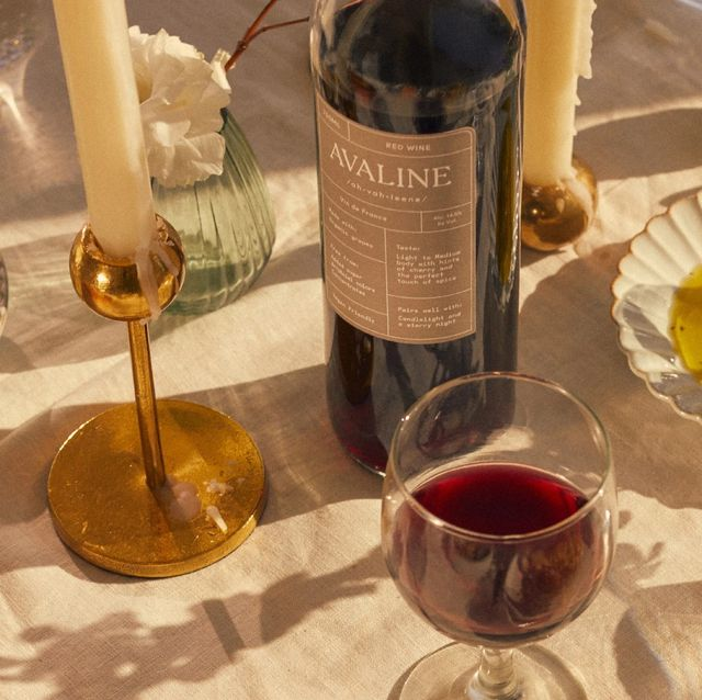 avaline red wine on table with candles, lemons, olive oil