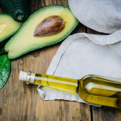 Avocado and avocado oil on a wooden background.