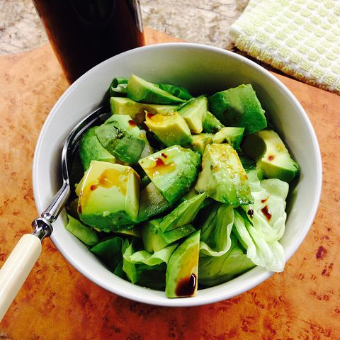 Avocado and butterhead lettuce salad with California olive oil and infused raspberry balsamic vinegar, with a fork on a cutting board