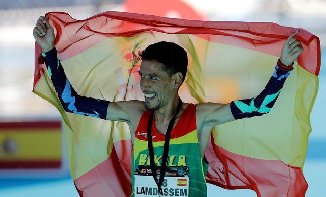 ayad lamdassem celebra envuelto en la bandera de españa el récord de españa de maratón logrado en valencia