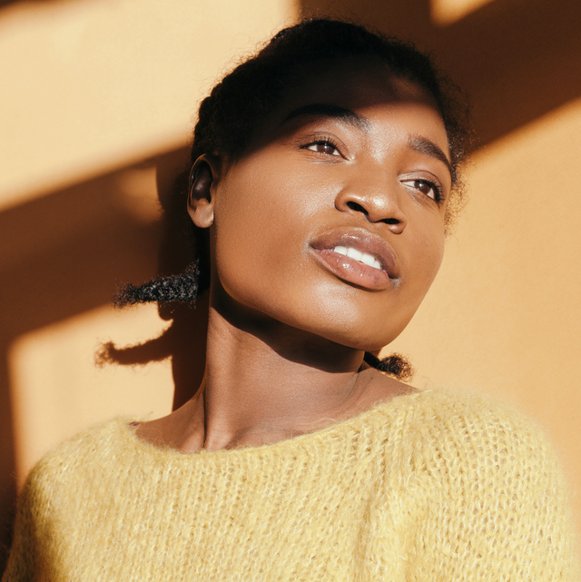 azelaic acid for skin   photo description a young black woman with smooth, bright skin standing in sunlight against a wall