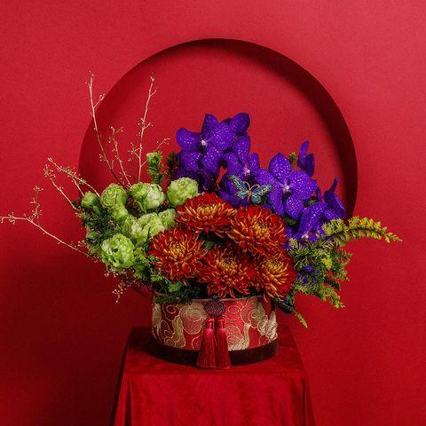 紅色背景前有紫色紅色綠色的花