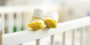 Baby booties on the edge of a cot