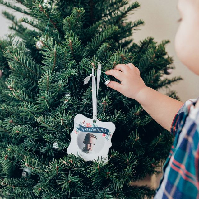 baby putting christmas ornament on tree