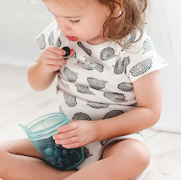 toddler with blueberries in a zip top food storage container