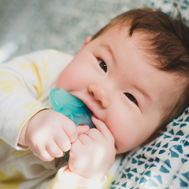 baby chewing on blue teether