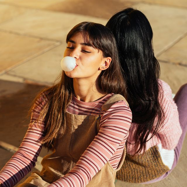 teen girl blowing bubble with gum in striped shirt and overalls