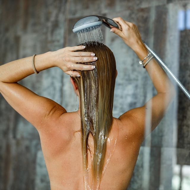 back view of a woman washing her hair under the shower