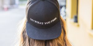 Back view of fashionable young woman wearing black baseball cap