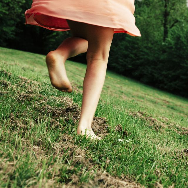 back view of girl running barefoot on a meadow, partial view