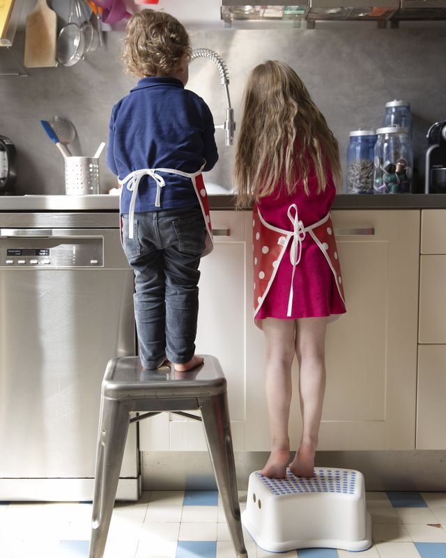 back view of little boy and girl washing dishes in the kitchen