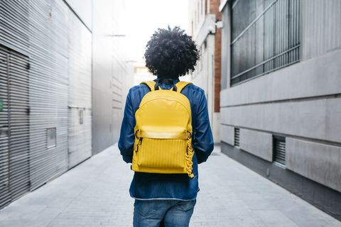 back view of young man with yellow backpack on e scooter in the city