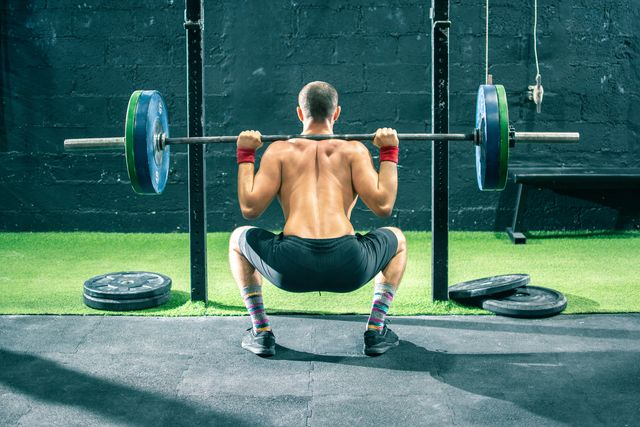 back view of young sportsman lifting a barbell at the gym