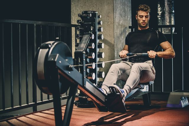 caucasian young man is using rowing machine for cardio training in the gym