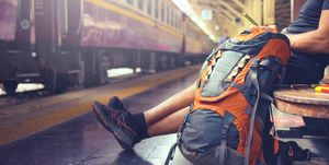 Backpacker use phone in railway station while waiting train . .
