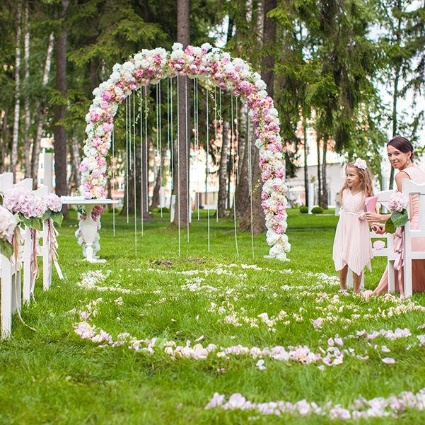 Backyard Wedding Ideas - Wedding benches with guests and flower arch for ceremony outdoors