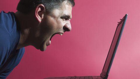 man schreeuwt naar laptop