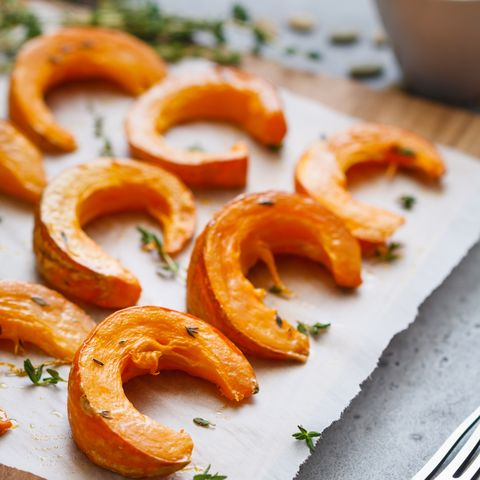 baked pumpkin slices with thyme on a wooden board over grey table seasonal food vegetarian recipe