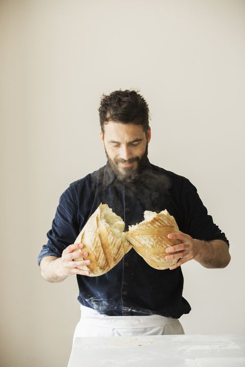 Baker holding two freshly baked loaves of bread.