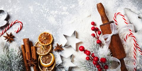 bakery background for cooking christmas baking with rolling pin, scattered flour and spices decorated with fir tree top view