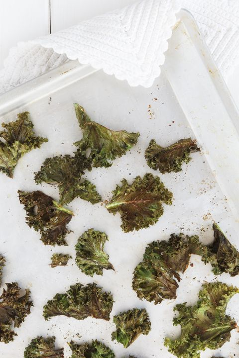 Baking tray of curly kale chips, elevated view