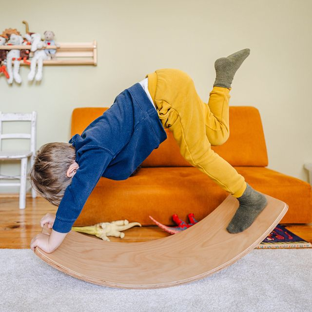 kid playing with balance board in play room