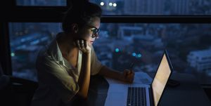 Woman is working with laptop at home during night.