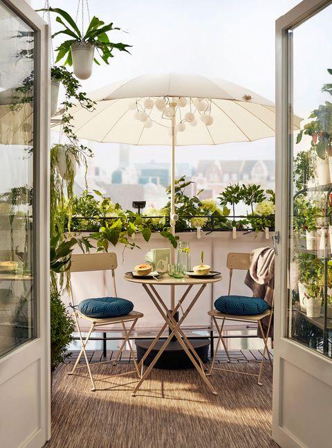 balcón decorado con una alfombra de exterior, mesa y dos sillas plegables, y una sombrilla