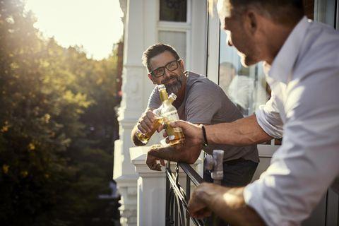 Dos hombres tomando una cerveza en el balcón durante el confinamiento