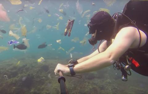 Bali diver swimming through plastic photo