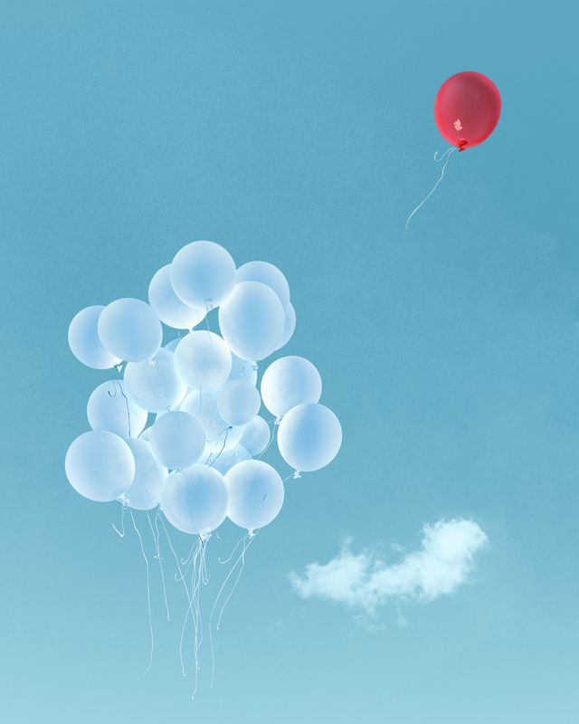 red balloon flying away from white balloons against blue sky