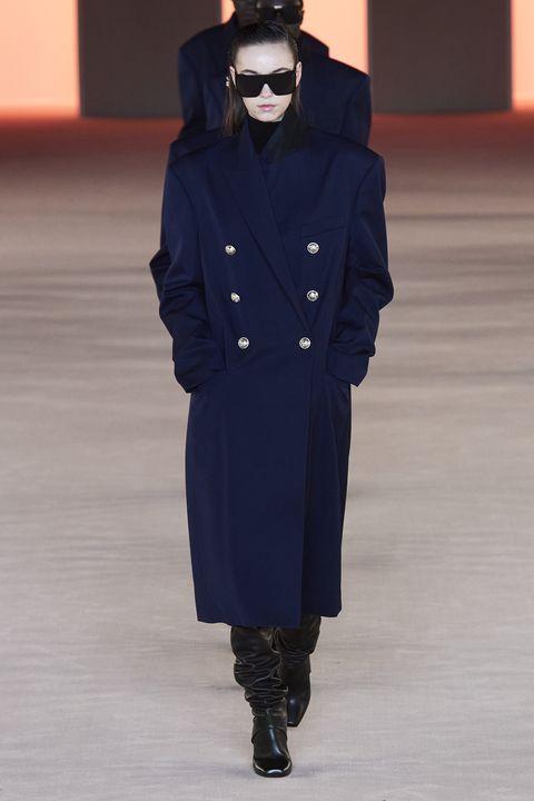 Fashion show, Runway, Fashion, Fashion model, Outerwear, Coat, Human, Overcoat, Fashion design, Joint,