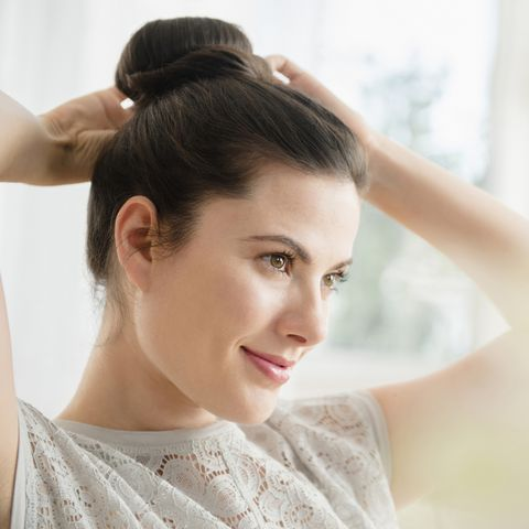 Caucasian woman tying hair in bun