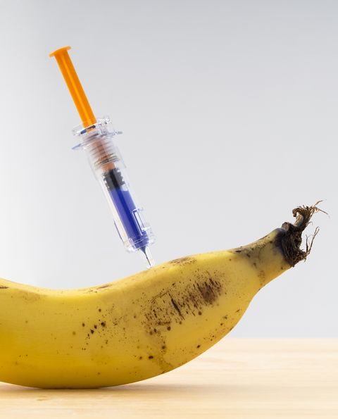 Banana potato with a laboratory syringe nailed to an experiment ; food concept transgenic and modified genetically.