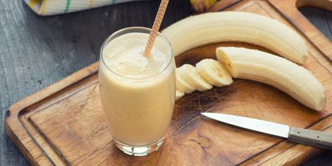 banana smoothie on wooden board with fresh bananas